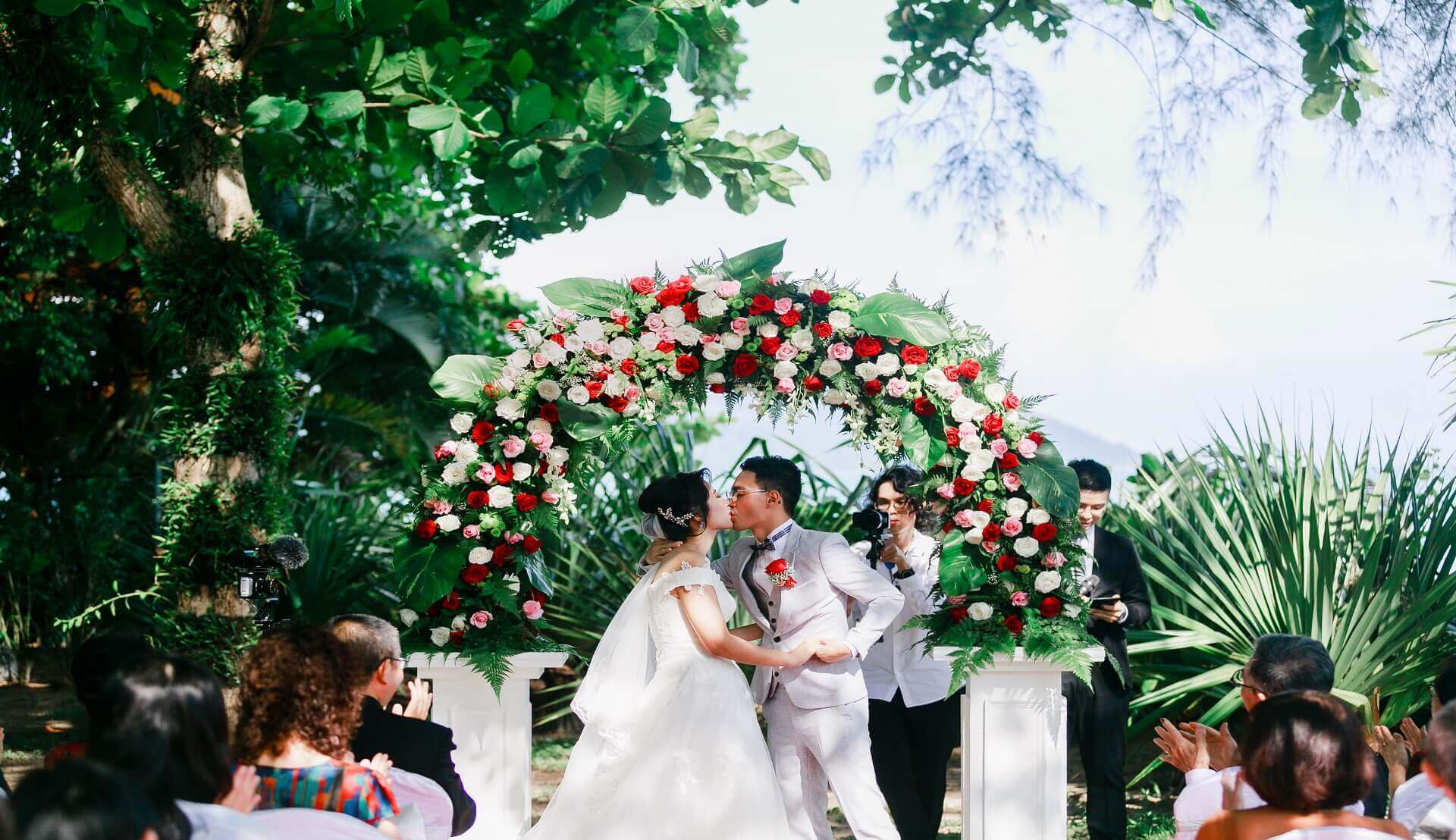 Sugar & Spice Events - Newlywed couple dip kiss outdoor ceremony flowers garden wedding beach floral arch